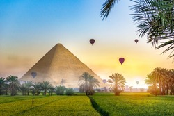 Air balloons over egyptian pyramid in green field at foggy morning. Fantasy landscape with egyptian pyramid