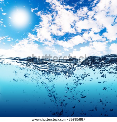 Air bubbles in ocean water rise to the surface with cloudy sky with sun in the background