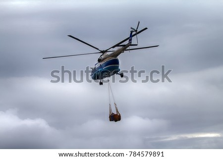 Air cargo and aviation work, air service lift helicopter carries sling (rope mesh) with empty metal barrels