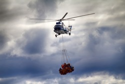 Air cargo and aviation work, lift helicopter in gloomy weather. Helicopter carries sling (rope mesh) with multicolored metal barrels