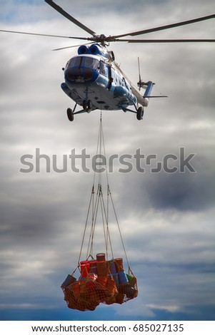 Air cargo and aviation work service using lift helicopter in gloomy weather. Helicopter carries sling (rope mesh) with multicolored metal barrels