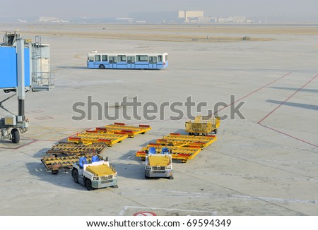 Air cargo equipment cars at the airport; at the background a bus for transporting the passengers