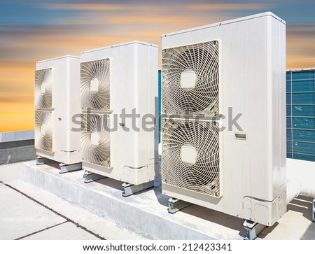 Air compressor machine on pedestal with sky background.