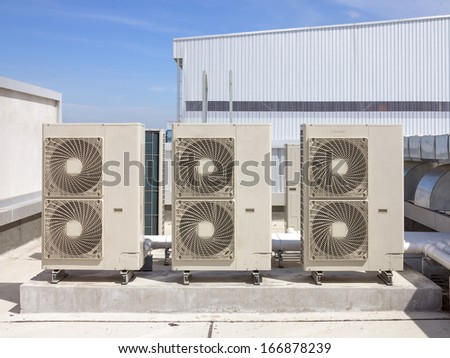 Air compressor on roof of factory with blue sky background.