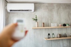 Air conditioner inside the room with woman operating remote controller. / Air conditioner with remote controller. Close up view of hand operating air conditioner remote control.