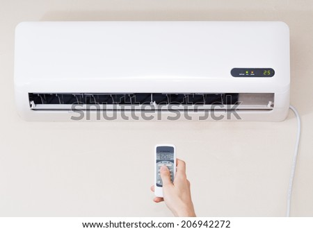 Air conditioner inside unit with man operating remote controller. / Air conditioner with remote controller