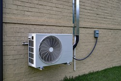 Air Conditioner mini split system mounted on brick wall with space for text copy