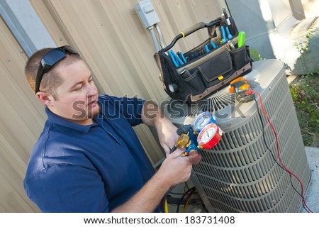 Air Conditioner Repair Man. Using testing equipment on outside unit.