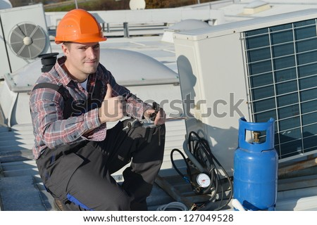 Air Conditioner Repairman Thumbs up, repairman working on a compressor and giving a thumbs up. Model is actual electrician.