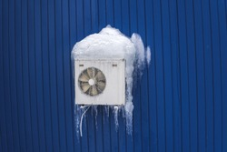 Air conditioning in ice, severe winter. White air conditioner
