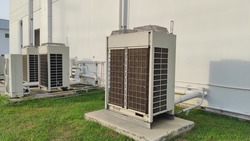 Air conditioning out door,A group of three industrial sized air conditioners along a brick wall,Air conditioning with extra door for maintenance