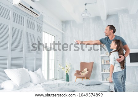 Air conditioning. Positive delighted joyful man standing together with his daughter and looking at the air conditioner while holding a remote control