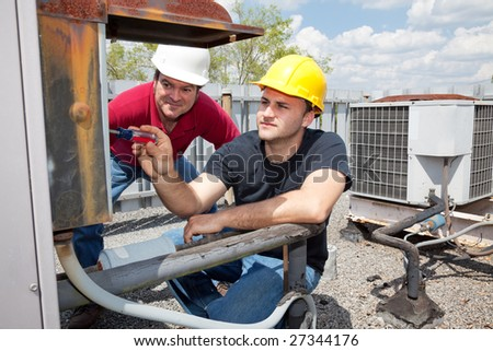 Air conditioning repair apprentice fixes an industrial compressor unit as his supervisor watches.