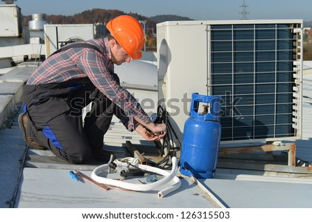 Air Conditioning Repair Young repairman on the roof fixing air conditioning system Model is actual electrician.