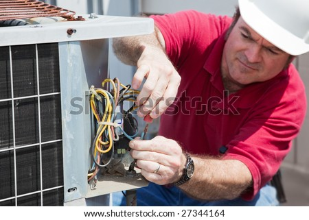 Air conditioning repairman rewiring a compressor unit.  Focus on the man's hands and the wires.