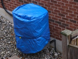 Air conditioning unit on red brick wall covered in blue tarp preparing for winter
