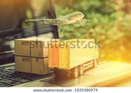 Air courier / freight forwarder or shipping service concept :  Boxes, a truck, white plane flies over a laptop, depicts customers order things from retailer sites via the internet and ship worldwide. #1039380979