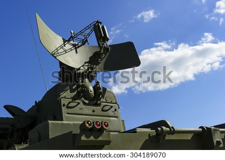 Air defense radar of military mobile mighty rocket launcher system of green color, modern army industry, white cloud and blue sky on background