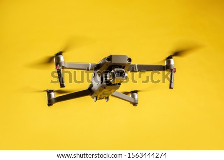 Air drone quadcopter isolated on yellow background in the air launched. Video and aerial photography from height.