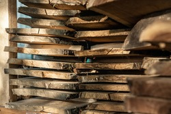 Air-drying sawn wooden plank slab pile under canopy at home backyard prepared for carpentry diy hobby. Woodshed store at house yard. Timber material stacked for woodworking .
