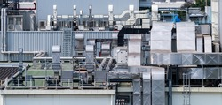 Air flow system of factory. Industrial ventilation. Air flow system on roof deck of manufacturing building. Ducts and pipe of ventilation system. Plant factory airflow of cooling system. Exterior.