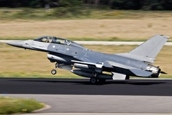 Air force fighter jet plane taking off from an airbase with full speed.