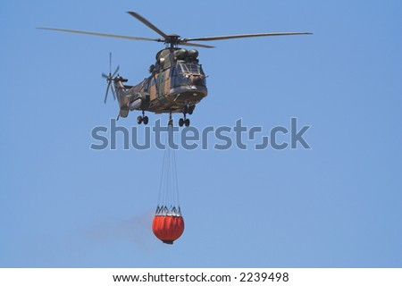 Air-Force Helicopter with a Bambi bucket filled to fight a forest fire