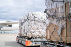 air freight cargo on dolly trailer waiting to be loaded onto aircraft