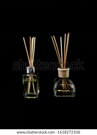 Air freshener on a black background. Incense sticks in a container with perfume. Aromatherapy canes in a glass bottle with aromatic oil
