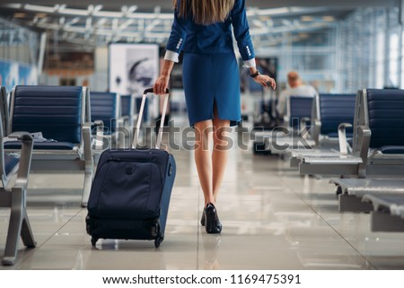 Air hostess going between seat rows in airport #1169475391