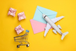Air mail, air delivery. Flat lay composition with airplane figure, gift boxes, shopping trolley and envelopes of letters on yellow background. Top view