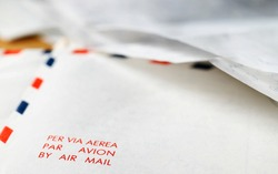 Air mail envelope letters  with several hand written sheets of letters lay on background , words AIR MAIL LETTER in focus