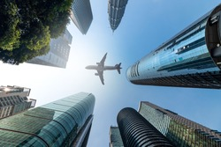 Air plane flying low over highrise office buildings in downtown of Malaysia City