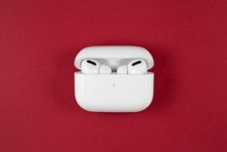 Air Pods Pro. with Wireless Charging Case. New Airpods pro on red background. Airpods Pro. Copy space