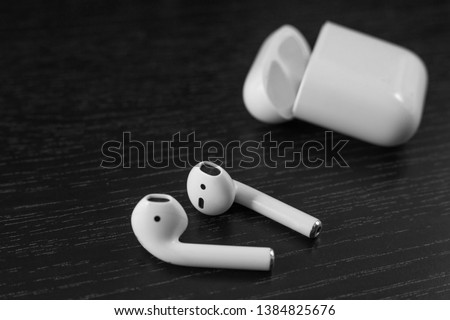 Air Pods. with Wireless Charging Case. New Airpods 2019 on black background. Airpods. Copy space #1384825676