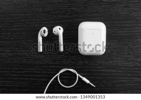 Air Pods with Wireless Charging Case. New Airpods 2019 on  black background. entangled 3.5 headphones  #1349001353