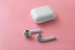 Air Pods. with Wireless Charging Case. New Airpods 2019 on pink background. Airpods. female headphones. EarPods.Copy Space