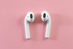 Air Pods. with Wireless Charging Case. New Airpods 2019 on pink background. Airpods. female headphones. EarPods