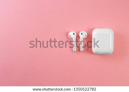 Air Pods. with Wireless Charging Case. New Airpods 2019 on pink background. Airpods. female headphones. entangled 3.5 headphones. Copy Space #1350522782