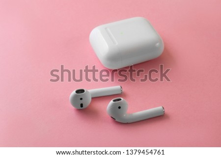 Air Pods. with Wireless Charging Case. New Airpods 2019 on pink background. Airpods. female headphones. entangled 3.5 headphones. Copy Space