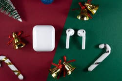 Air Pods. with Wireless Charging Case. New Airpods 2020 on red and green background. Air Pods on Christmas background. christmas headphones