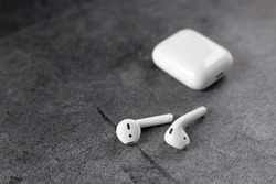 Air Pods. with Wireless Charging Case. New Airpods on  scratch metal background. Airpods. female headphones. copy space