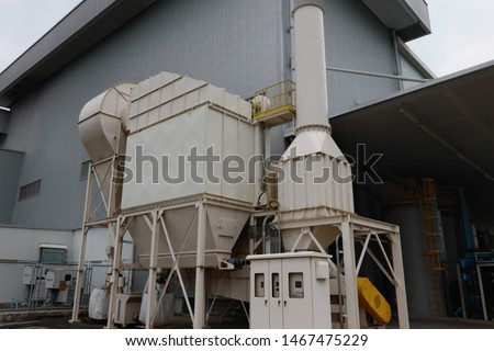 Air pollution control equipment as dust filter collection and chimney stack locates out of industrial building.