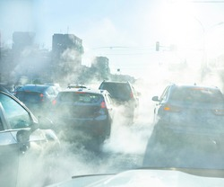 air pollution from the exhaust of cars in the city during the cold day, environmental pollution in the city