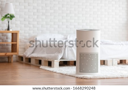 Photo of  Air purifier in cozy white bedroom for filter and cleaning removing dust PM2.5 HEPA in home,for fresh air and healthy life,Air Pollution Concept
