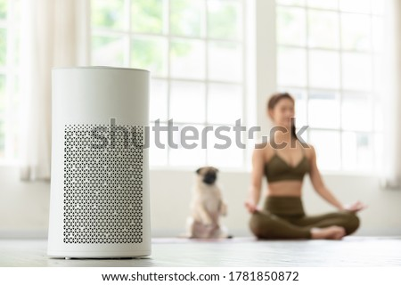 Air purifier in cozy white Living room for filter and cleaning removing dust PM2.5 HEPA at home with woman exercise yoga with dog in background,for fresh air and healthy life,Air Pollution Concept