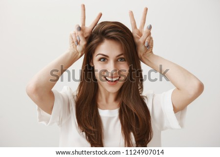 Air quotes concept. Portrait of attractive joyful caucasian woman with beautiful smile raising hands near head and showing v sign or peace, mimicking bunny ears while standing over gray background stock photo