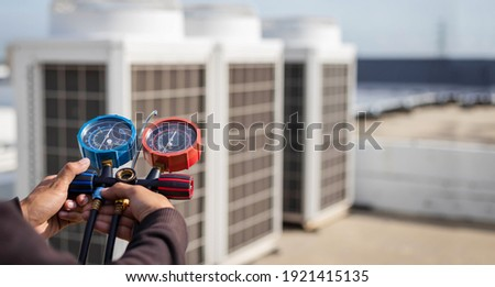 Air repair mechanic using measuring equipment for filling industrial factory air conditioners and checking maintenance outdoor air compressor unit.