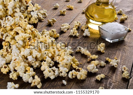 Air salty popcorn.A bowl of popcorn on a wooden table.Salt popcorn on the wooden background .  With space for text.Top view.popcorn texture.Chees .  #1155329170