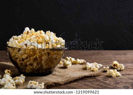 Air salty popcorn.A bowl of popcorn on a wooden table.Salt popcorn on the wooden background .  With space for text.Top view.popcorn texture.Chees .